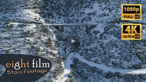 Aerial Footage. Snowy mountain has a train bridge.
